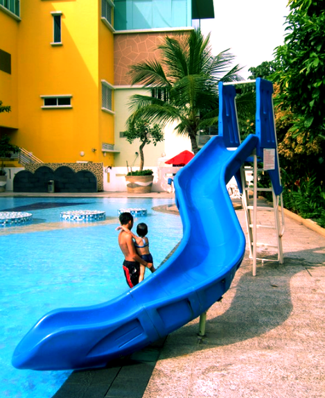 blue adams custom pool slide next to hotel in Asia.